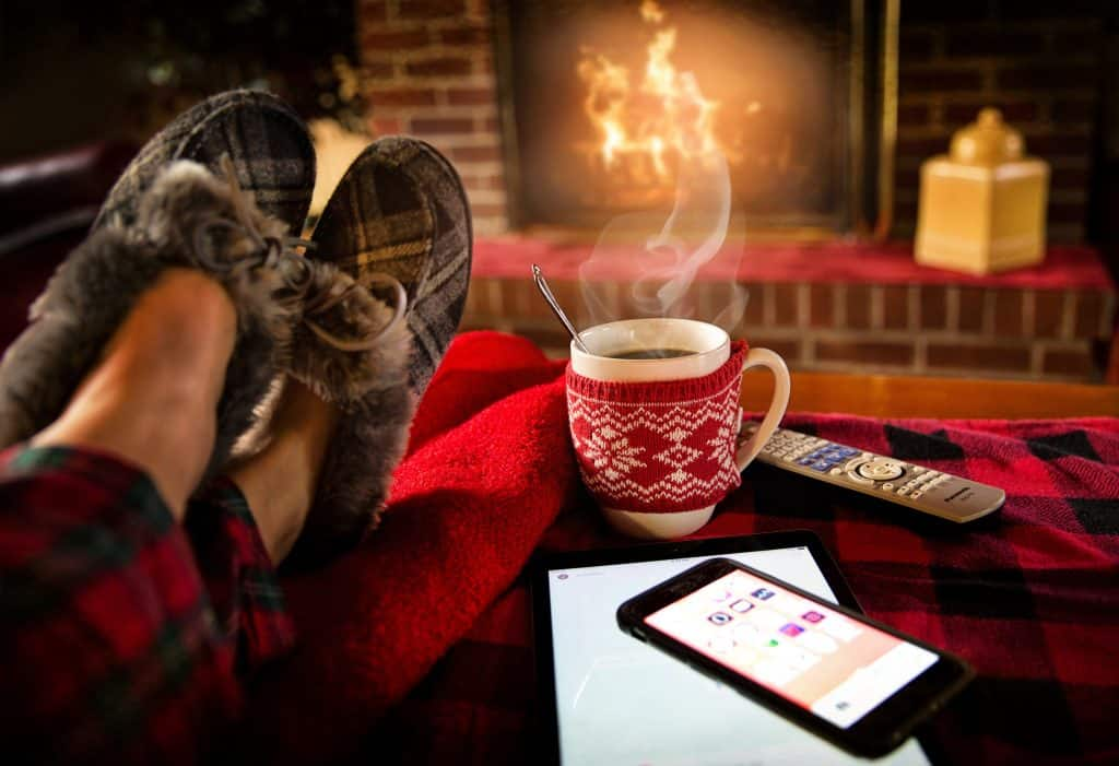 Image of someone's feet put up in warm house shoes in front of a fireplace, a steaming mug of coffee next to them.