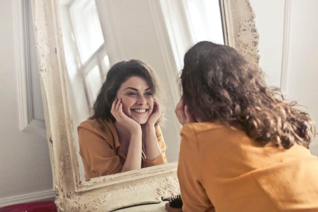 Image of a young woman smiling at herself in the mirror