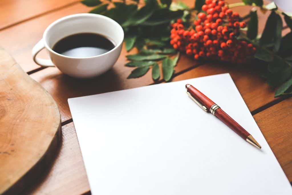 Image of a blank piece of paper, a pen and a cup of coffee