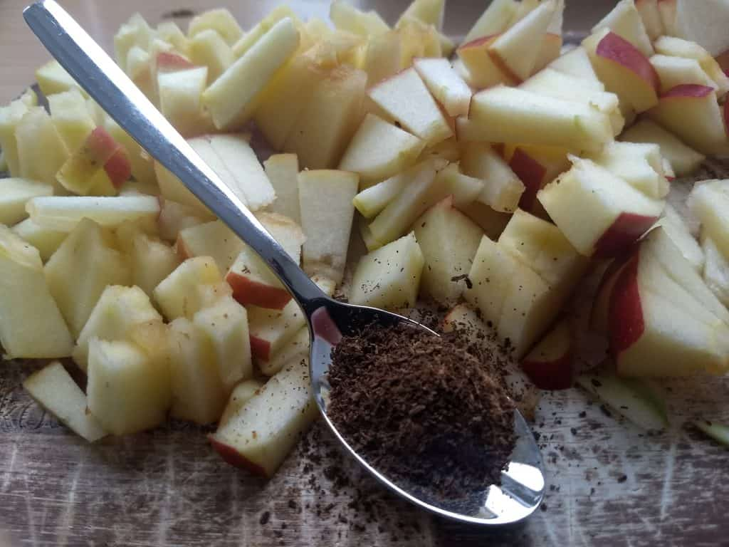 Image of a chopped up apple and a spoonful of cinnamon for the quinoa breakfast recipe