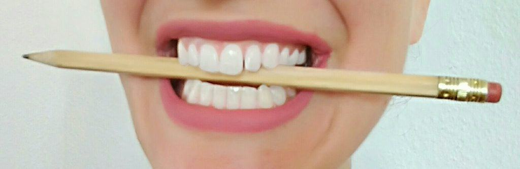 How to be in a better mood - smiling with a pencil between the teeth