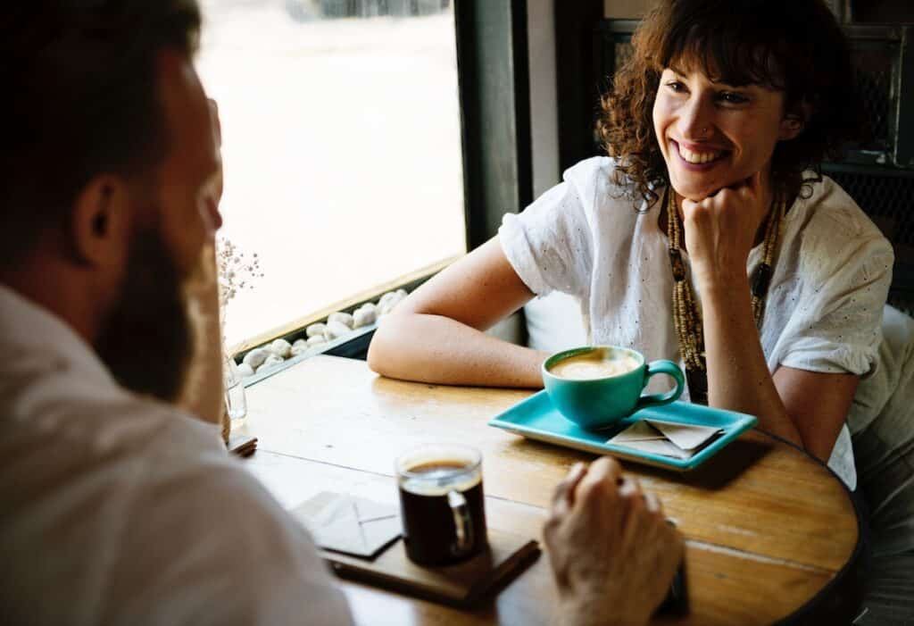 Image of two people being social over a cup of coffee
