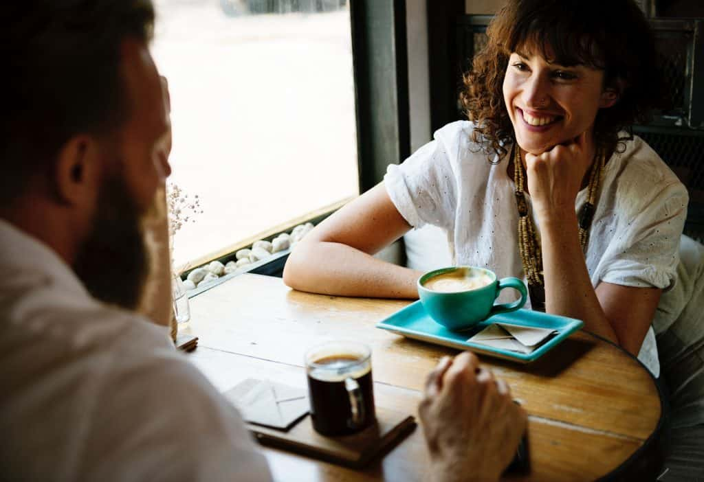 Two people in an engaged conversation over a cup of coffee