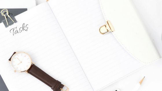 A blank task list in a white notebook, a wrist watch on top.