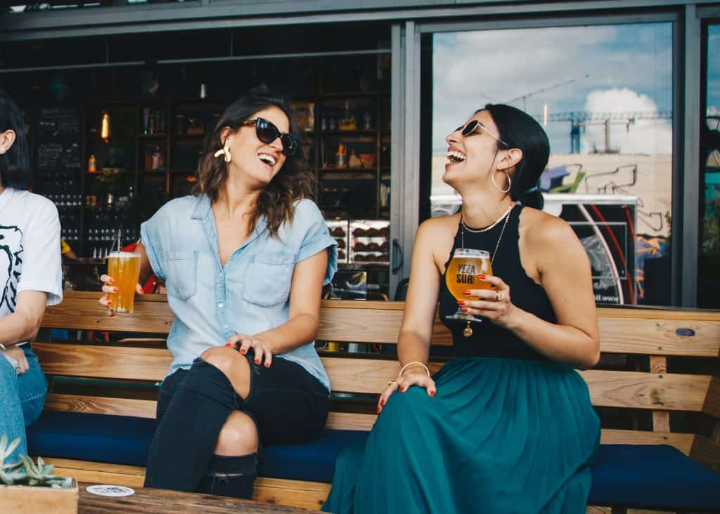 Two female friends laughing together, mimicking each other's body language.