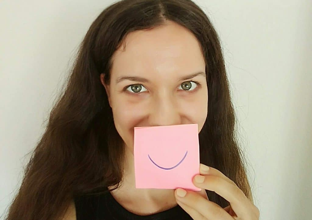 Image of a woman holding a post-it with a smile drawn on in front of her face, symbolising a genuine smile which is one of the qualities of a likeable person