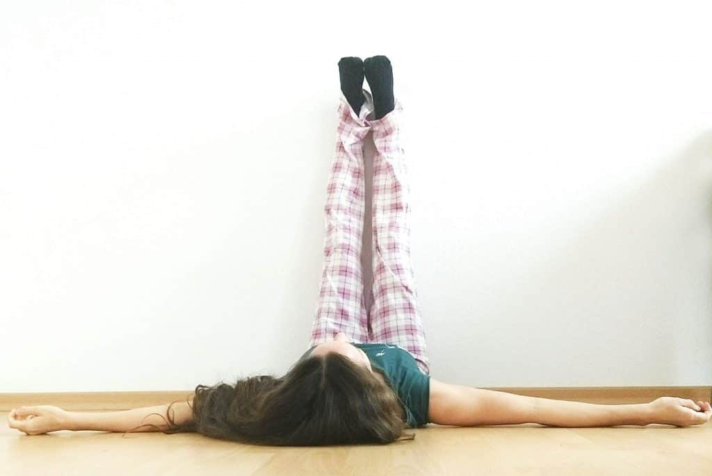 image of a woman in Legs up the wall pose, a yoga pose very helpful for a clogged lymphatic system and to get rid of water retention