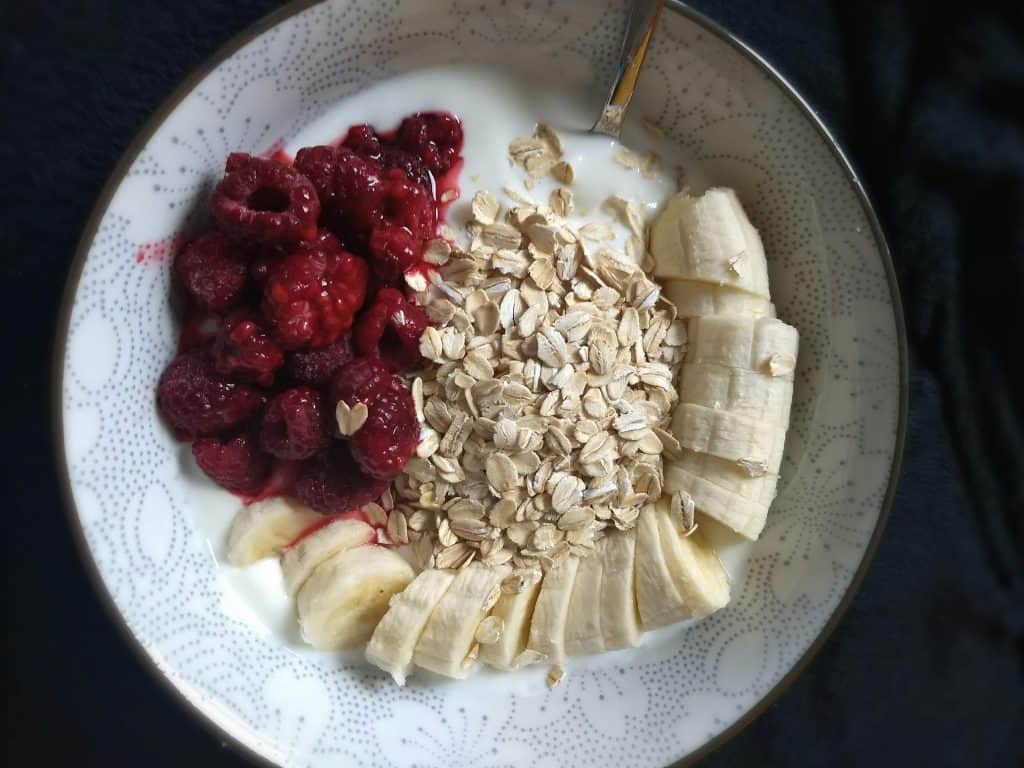 An oatmeal porridge bowl with banana and raspberries - the whole load of protein you need for faster hair growth!