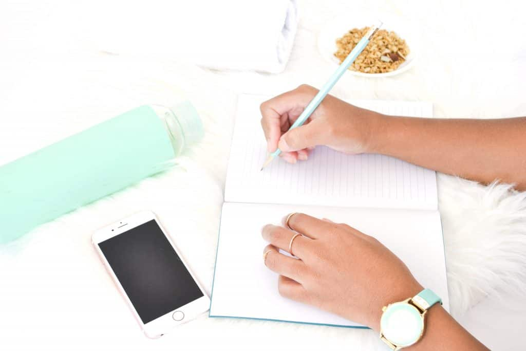 Image of someone writing in a blank notebook