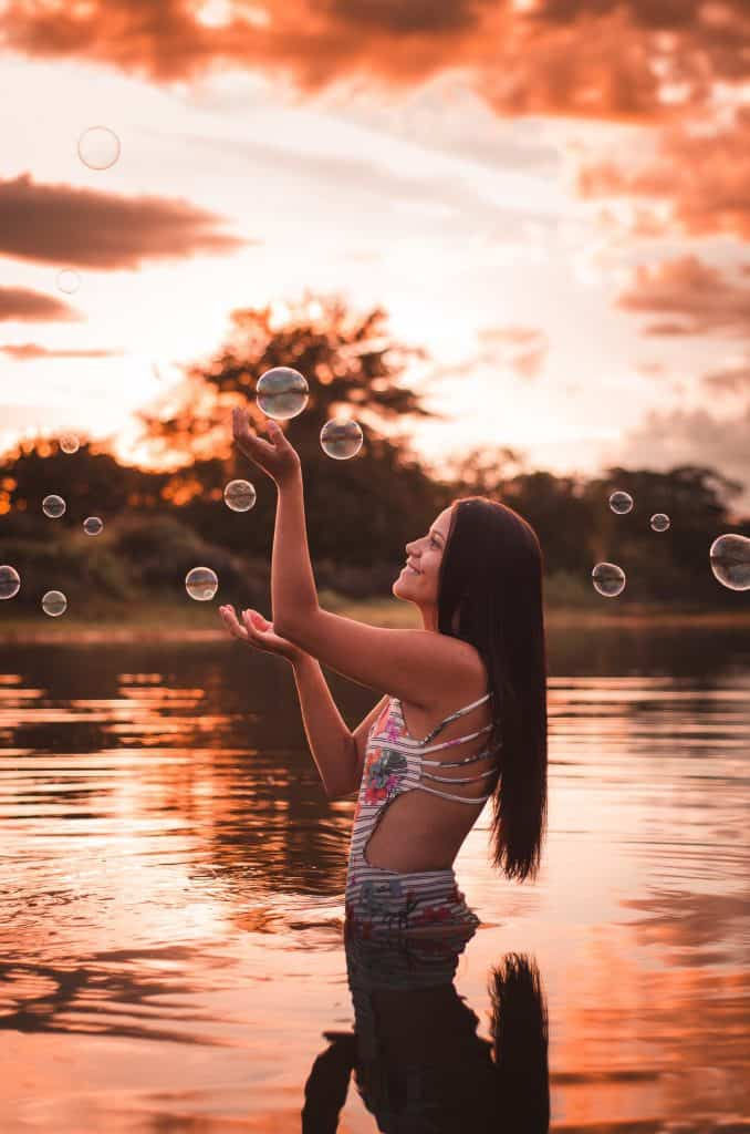 Image of a dark-haired woman with hair type 1c. The woman stands in the water and plays with bubbles.