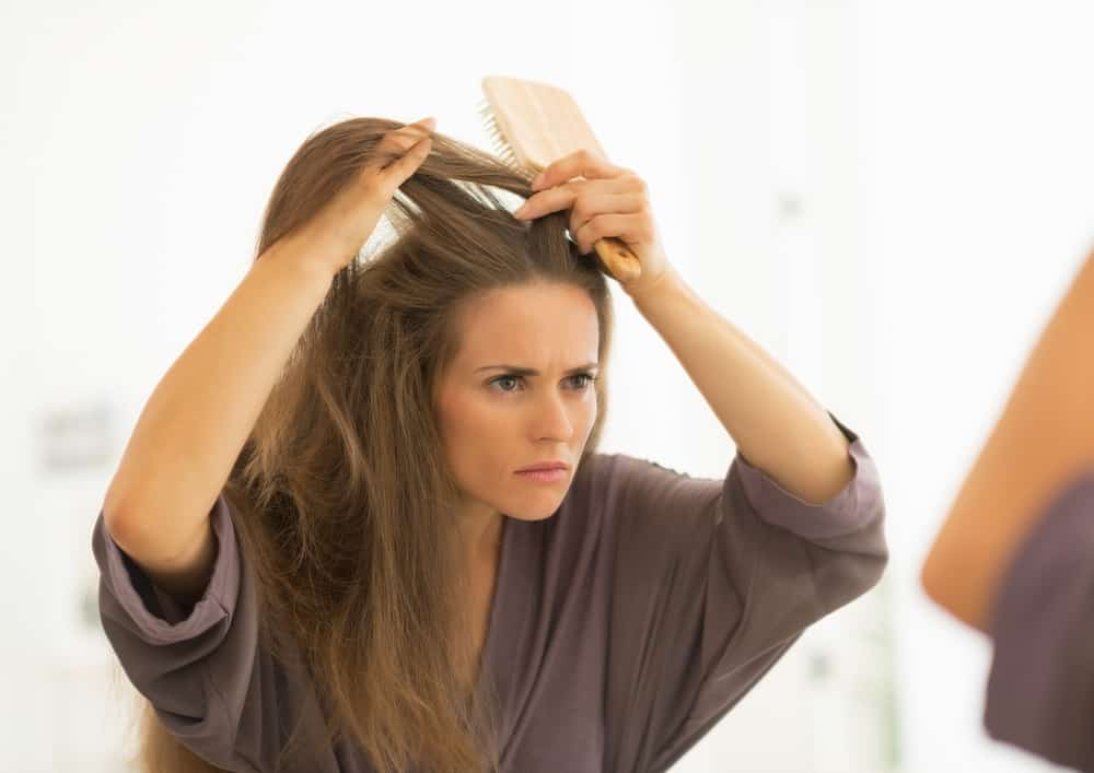 Image of a woman with long hair inspecting her dandruff in the mirror