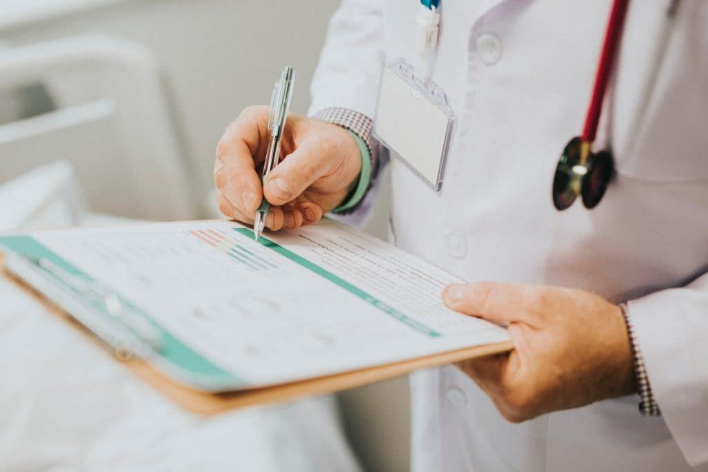 Image of a medical professional in a white suit writing something on a clipboard