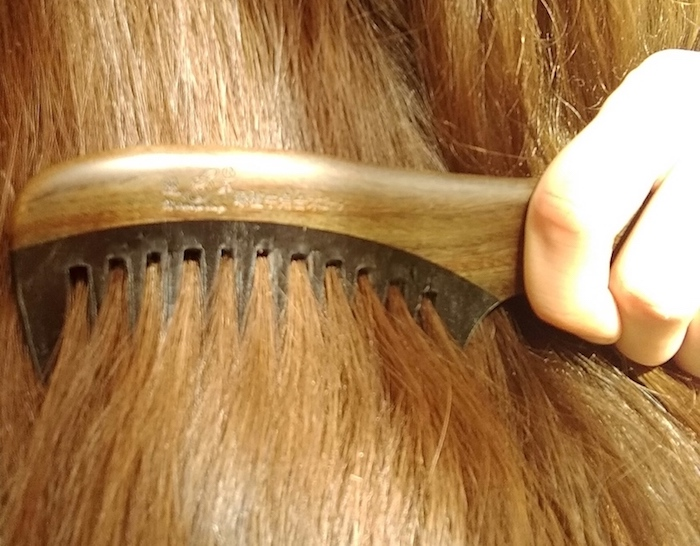 Image of a wooden comb combing through shiny, moisturised hair