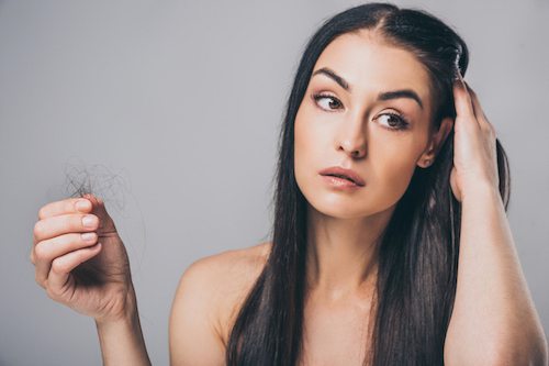 Image of a woman with hair loss, holding some hair in her right hand
