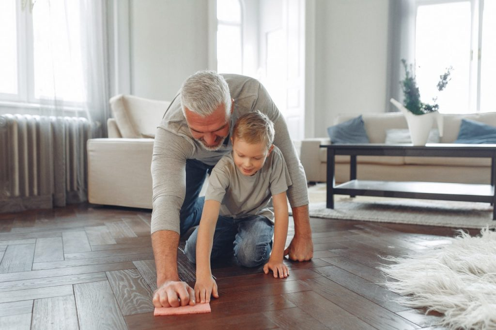Image of a grey-haired man and a blonde boy wiping a wooden floor together