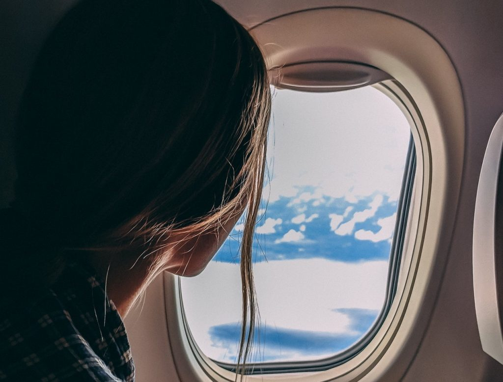 Image of a woman looking out of a plane window