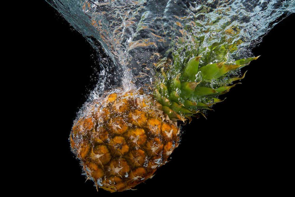 Image of a pineapple falling into water, ready to be made into a homemade face mask without honey or yogurt