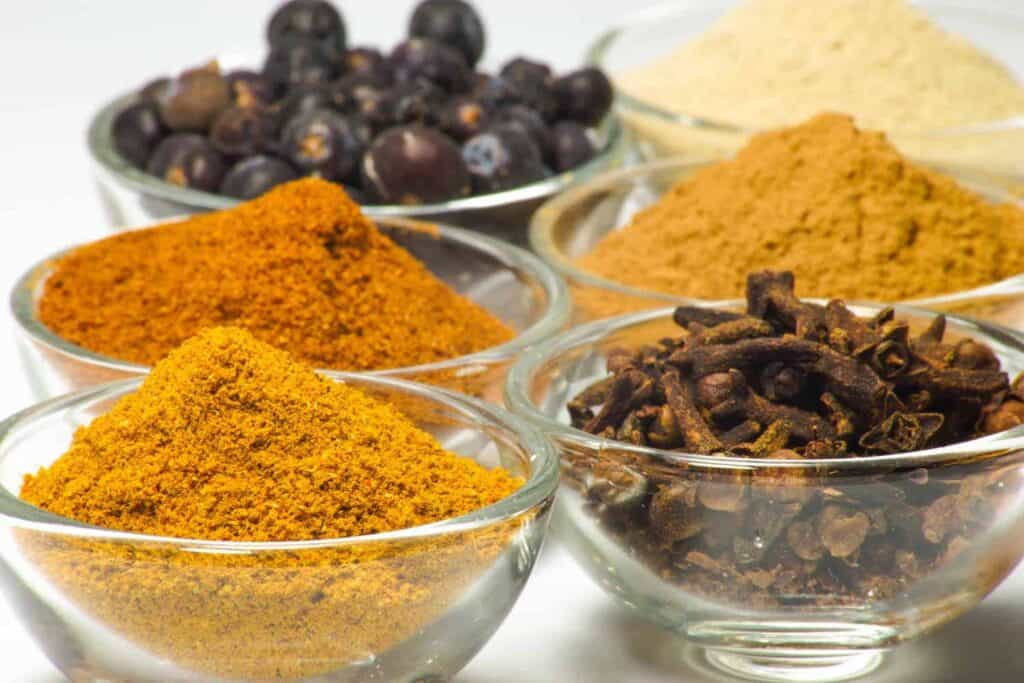 Image of spices in little glass bowls, lined up to be used for a DIY turmeric face mask without honey