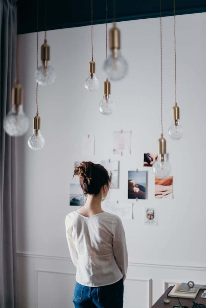 Image of a woman standing in front of her vision board, imagining her goals as fulfilled, getting more motivated