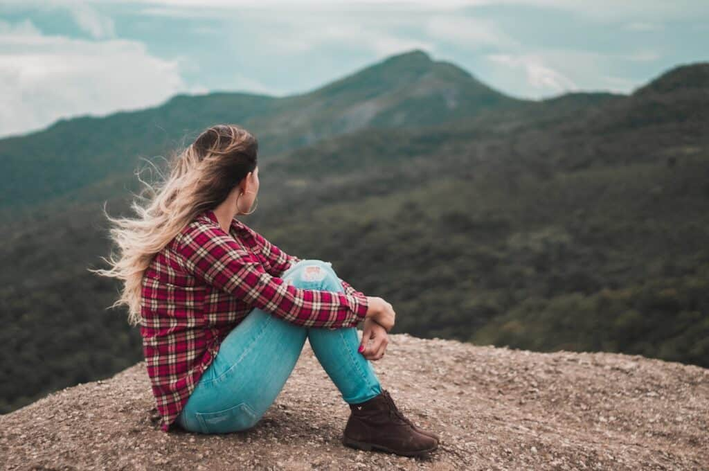 Image of a woman sitting on top of a mountain, wind in her hair, looking down into the valley