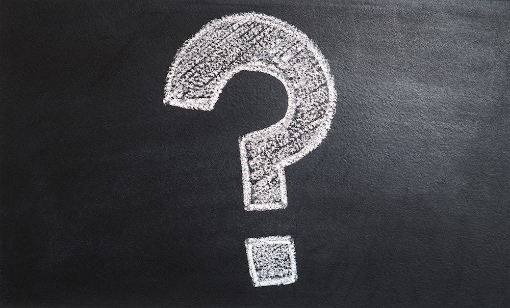 Image of a a white chalk question mark on a black board