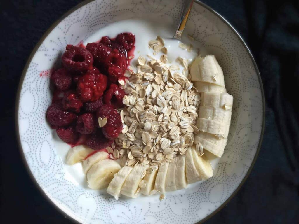 Image of an oatmeal porridge bowl with banana and raspberries - the whole load of protein you need for faster hair growth!