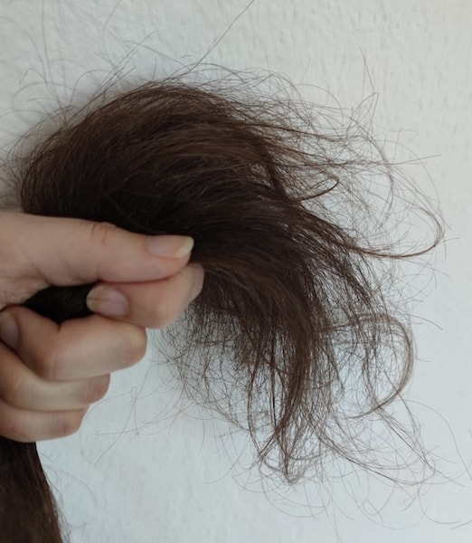Image of a hand holding hair ends to check for split ends